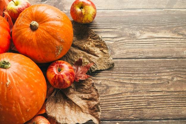 Calabazas de otoño en mesa de madera con hojas