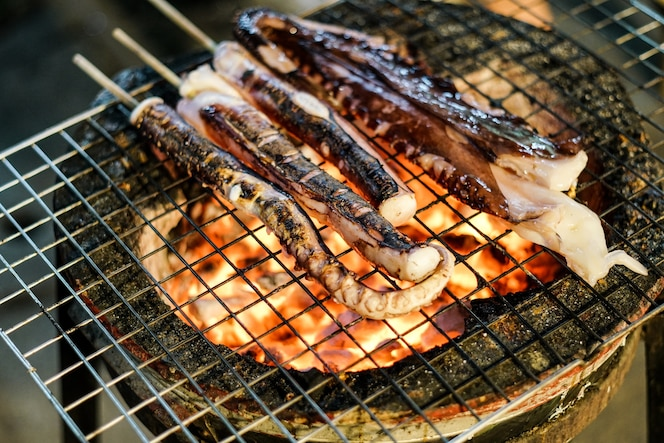 Calamar a la parrilla o mano de pulpo cocina en la estufa, mariscos tradicionales de la cocina tailandesa de la calle