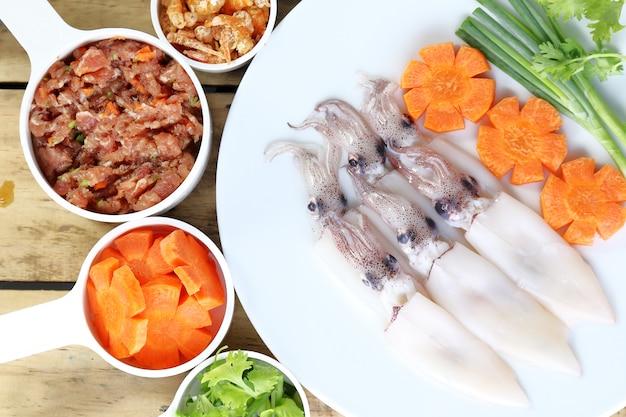 Calamares crudos, zanahoria y cerdo, preparar para cocinar.