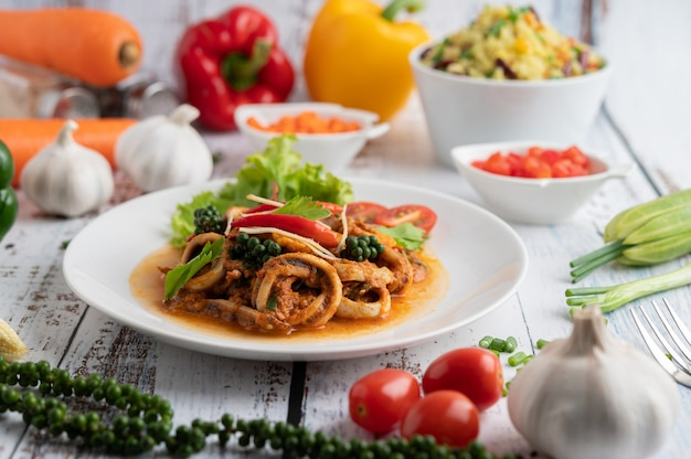 Calamares fritos con pasta de curry en plato blanco, con verduras y guarniciones sobre un piso de madera blanca.