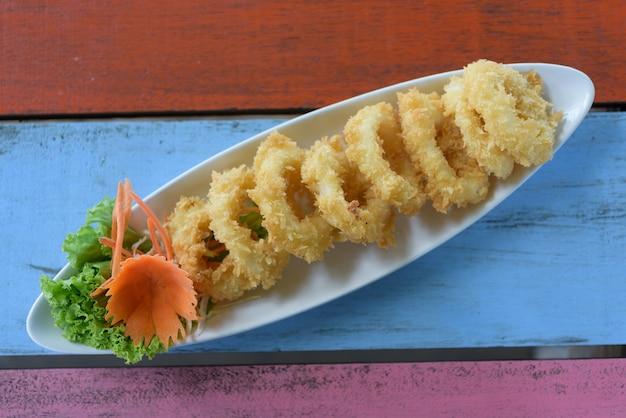 Calamares fritos rebozados en calamares en mesa de madera vintage, vista superior