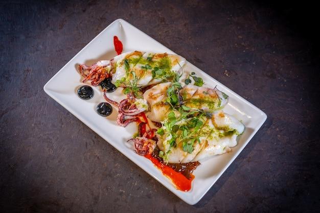 Calamares fritos con salsa sobre un fondo negro, sobre una placa blanca.