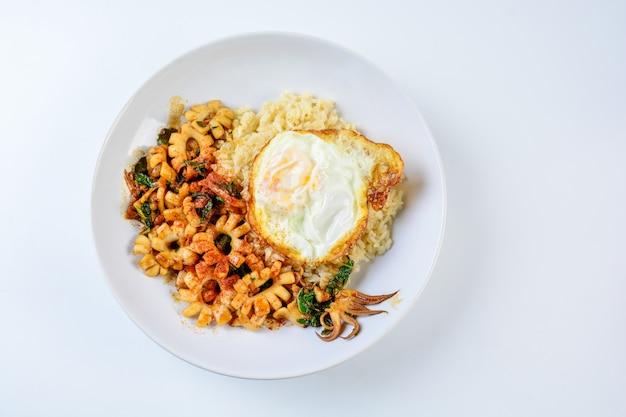 Calamares salteados picantes con hojas de albahaca y chile, huevo sunny side up, servido con arroz integral
