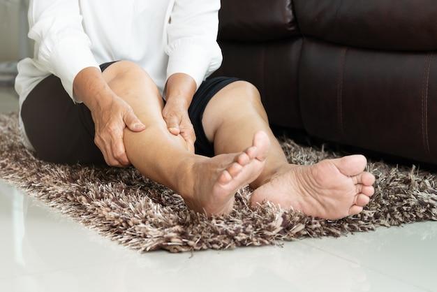 Calambre en la pierna, mujer mayor que sufre de dolor en la pierna, dolor en el hogar, problema de salud