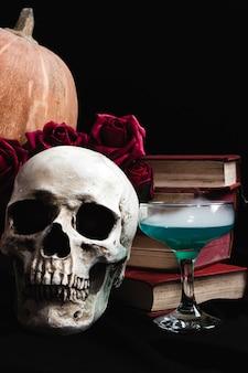 Calavera con bebida verde, libros y rosas.