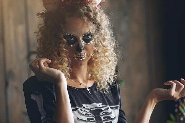 Calavera de maquillaje de halloween hermosa mujer con peinado rubio. niña modelo santa muerte en traje negro.