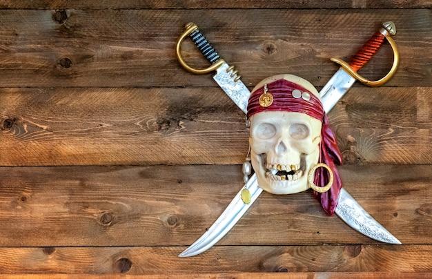 Calavera pirata alegre en pañuelo con espadas cruzadas y dientes de oro en madera
