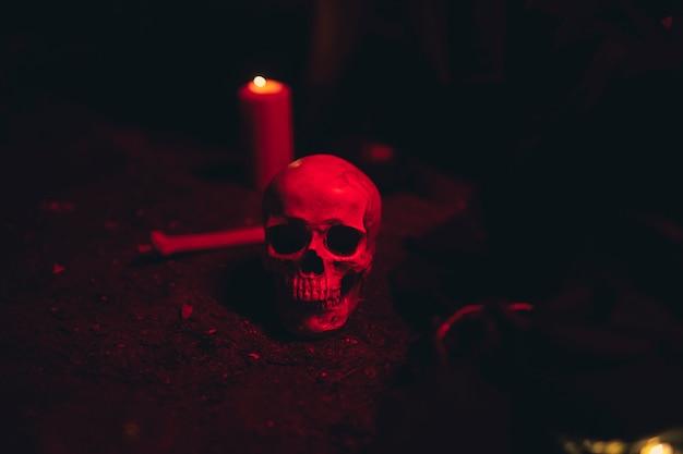Calavera y vela en una luz roja oscura