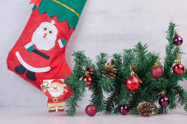 Calcetín de navidad lleno de bolas festivas sobre superficie blanca