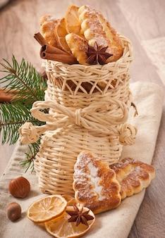 Calcetín de navidad de mimbre lleno de galletas, canela, limón confitado y anís estrellado
