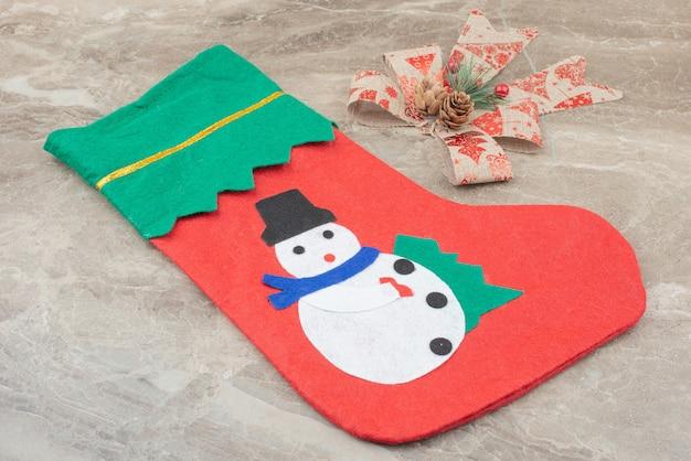 Calcetín navideño y cinta sobre mármol.