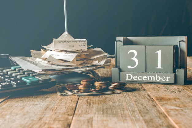 Calcula el dinero de la calculadora en la mesa de madera. 31 de diciembre