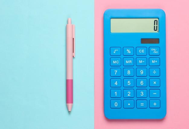 Calculadora azul con bolígrafo sobre azul rosa.