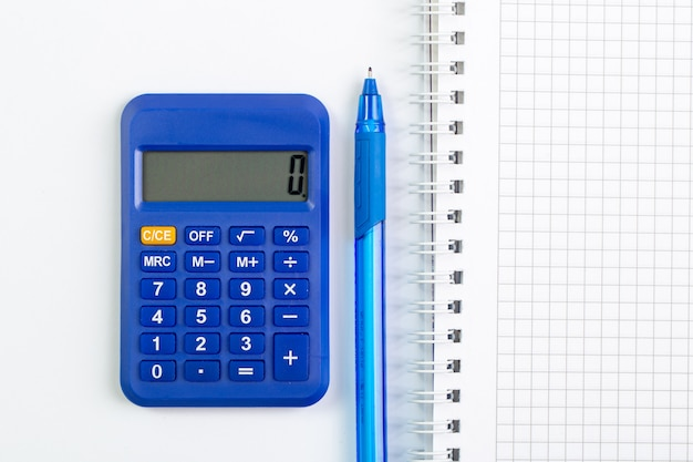 Calculadora azul junto con bolígrafo azul y cuaderno