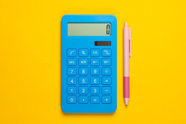 Calculadora azul con lápiz sobre amarillo.
