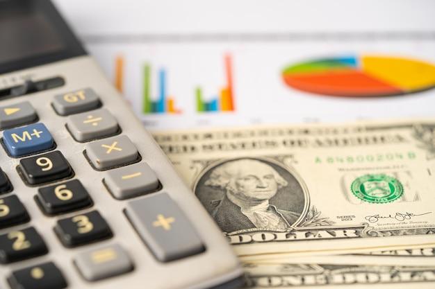 Calculadora en billetes de dólares estadounidenses y papel cuadriculado.