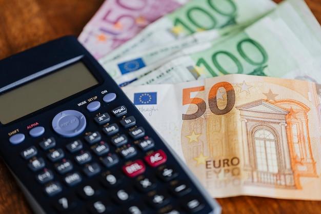 Calculadora y billetes en euros en una mesa