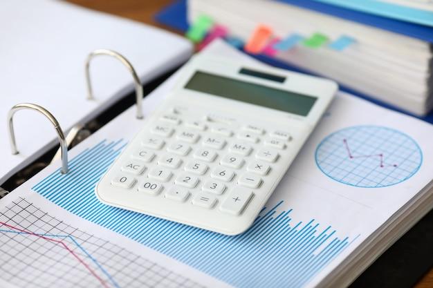 La calculadora blanca con carta de negocios se encuentra en la oficina
