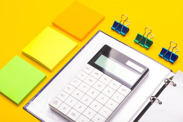 Calculadora en el bloc de notas y pegatinas siguiente aislado sobre fondo amarillo