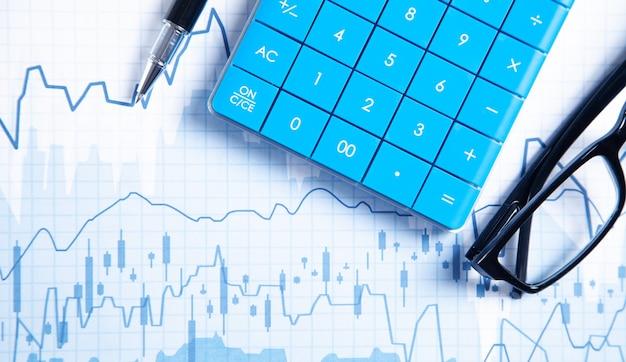 Calculadora, bolígrafo, anteojos en gráficos financieros. negocio. análisis