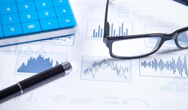 Calculadora, bolígrafo, anteojos en gráficos financieros