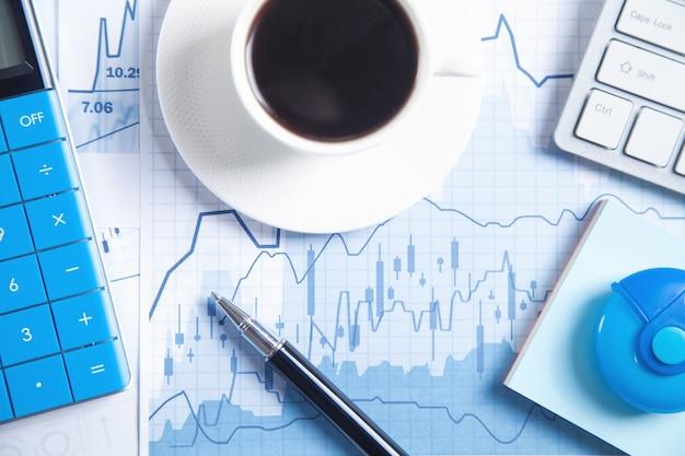 Calculadora, bolígrafo, café en gráfico financiero