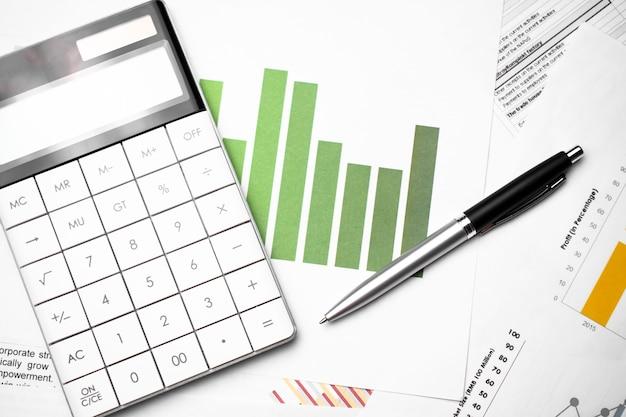 Calculadora y bolígrafo con gráfico de negocios verde