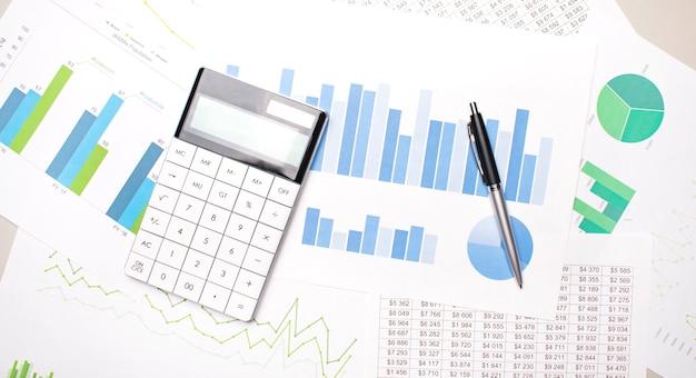 Calculadora y bolígrafo con gráficos sobre una mesa