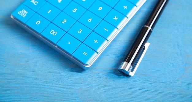 Calculadora y bolígrafo sobre fondo azul.