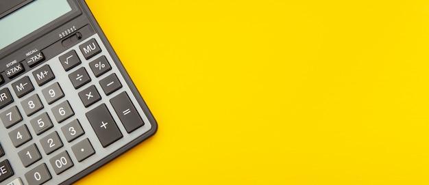 Calculadora en un concepto amarillo estirado del espacio, del negocio y de las finanzas