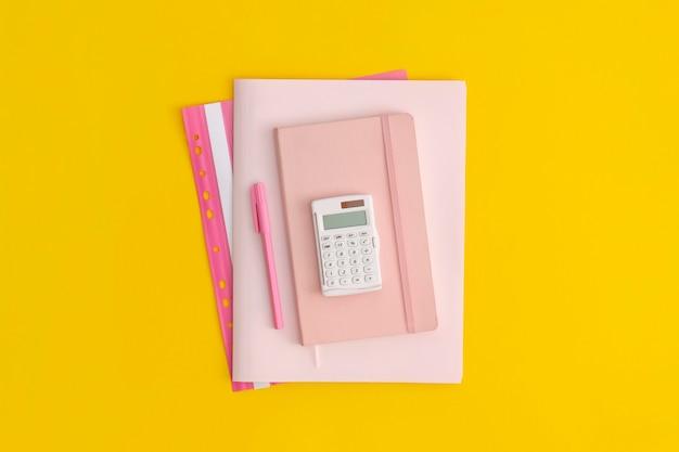 Calculadora, cuaderno y bolígrafo sobre fondo amarillo. vista superior. endecha plana. concepto de regreso a la escuela.
