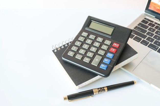 Calculadora en el cuaderno con la pluma cerca de la computadora portátil