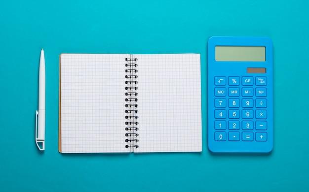 Calculadora con cuaderno sobre fondo azul. proceso educativo. vista superior. endecha plana