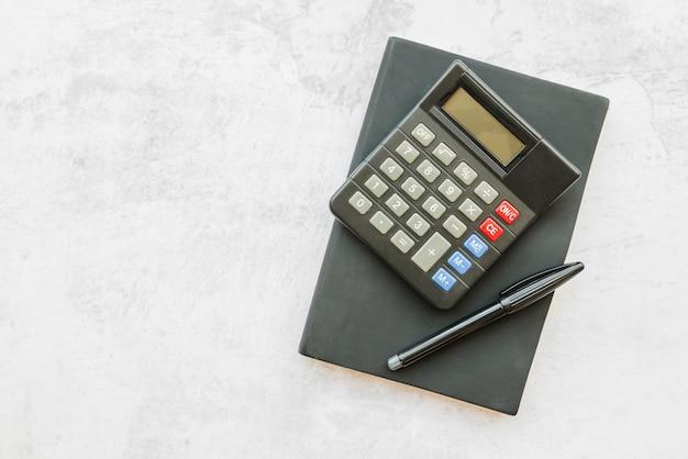 Calculadora con cuaderno sobre mesa