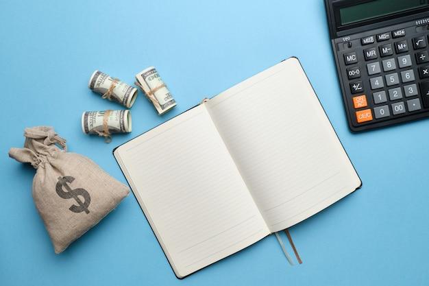 Una calculadora, un diario junto a una bolsa de dinero.