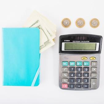 Calculadora con dinero y cuaderno en la mesa