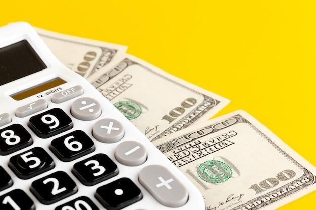 Calculadora y dólares sobre fondo amarillo