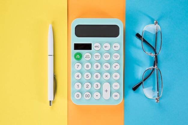 En la calculadora de escritorio, bolígrafo y gafas. papel multicolor