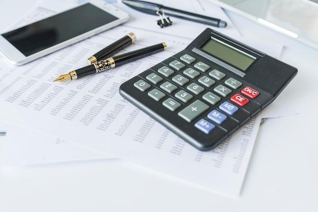 Calculadora en escritorio con documentos y teléfono inteligente.