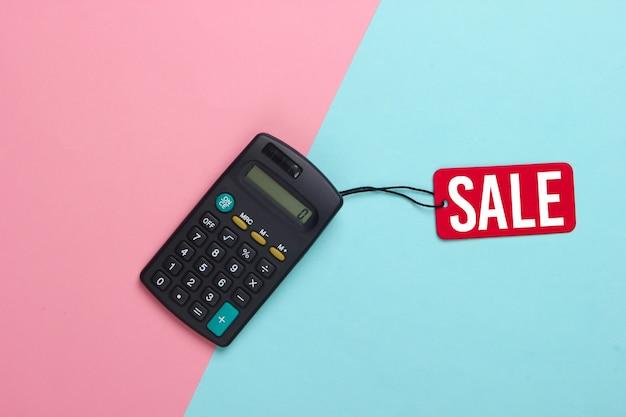 Calculadora con una etiqueta de venta roja sobre azul rosa. gran venta, descuentos, compras.