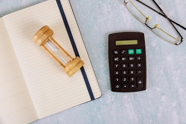 La calculadora y las gafas en el bloc de notas abierto fecha límite de reloj de arena como el paso del tiempo del contador.