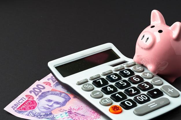 Calculadora con hucha y dinero, hryvnas ucranianas