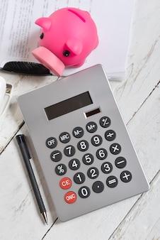 Calculadora y hucha en una mesa de madera blanca