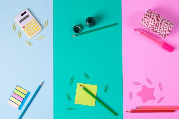 Calculadora, lápiz de color, sujetapapeles, sobre fondo de papel azul pastel, rosa, azul