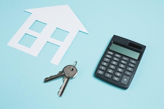 Calculadora y llaves con recorte de papel de la casa sobre fondo
