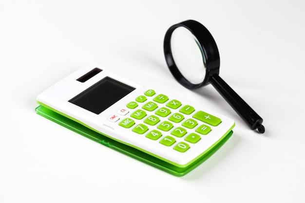 Calculadora con una lupa sobre un fondo blanco.
