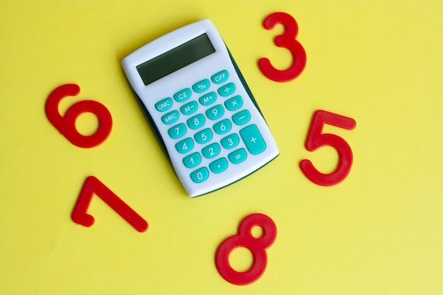 Calculadora matemática de fondo y números sobre fondo amarillo, plano laical