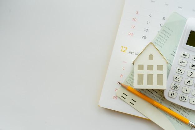 Calculadora, modelo de hogar, lápiz amarillo, libro de cuentas bancarias y calendario sobre fondo blanco para préstamo hipotecario