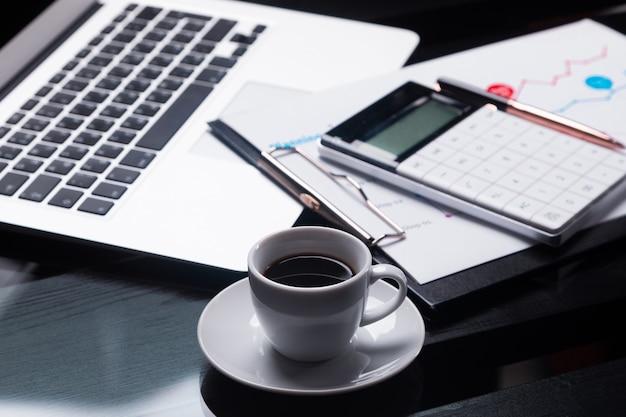 La calculadora moderna está en el cuaderno y en la hoja con el horario al lado de la taza de café