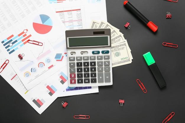 Calculadora moderna y documentos con dinero en superficie oscura